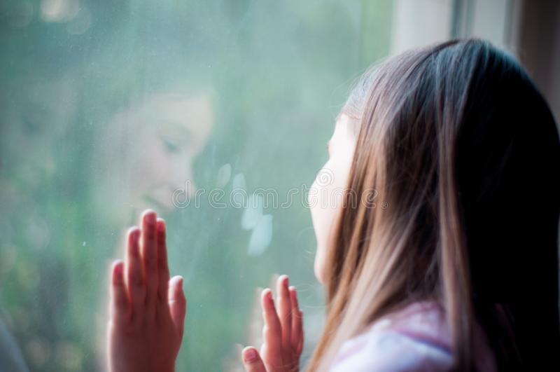 Little girl looks out the window at her reflection in the glass on a summer day royalty free stock photography
