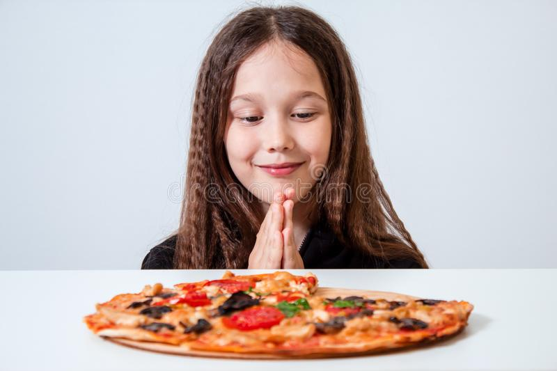 The little girl looks at the pizza. The child prays before eating stock image
