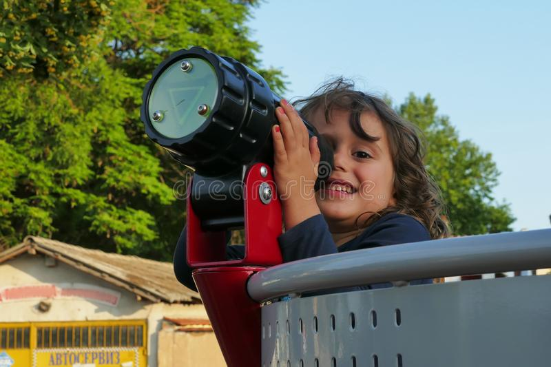 The little girl looks through a telescope stock image