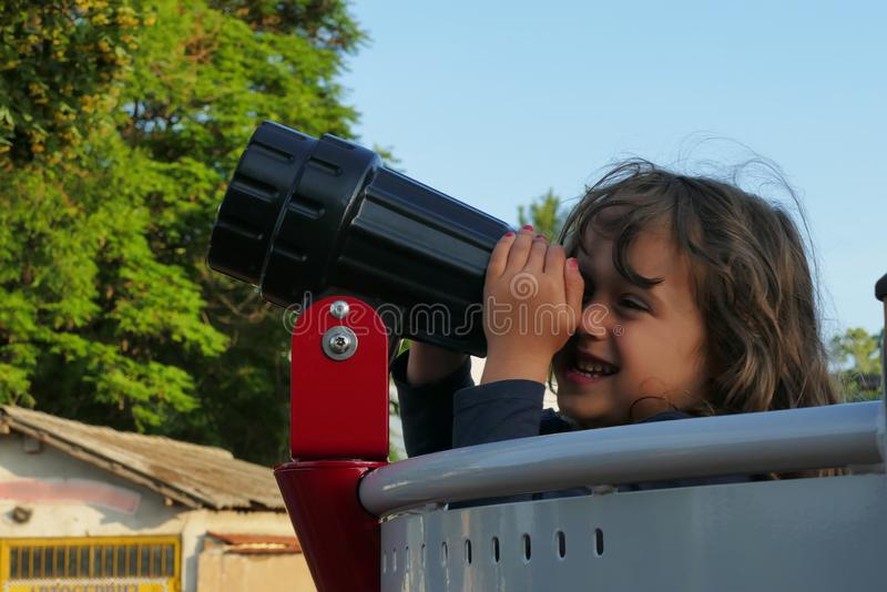 The little girl looks through a telescope royalty free stock photo
