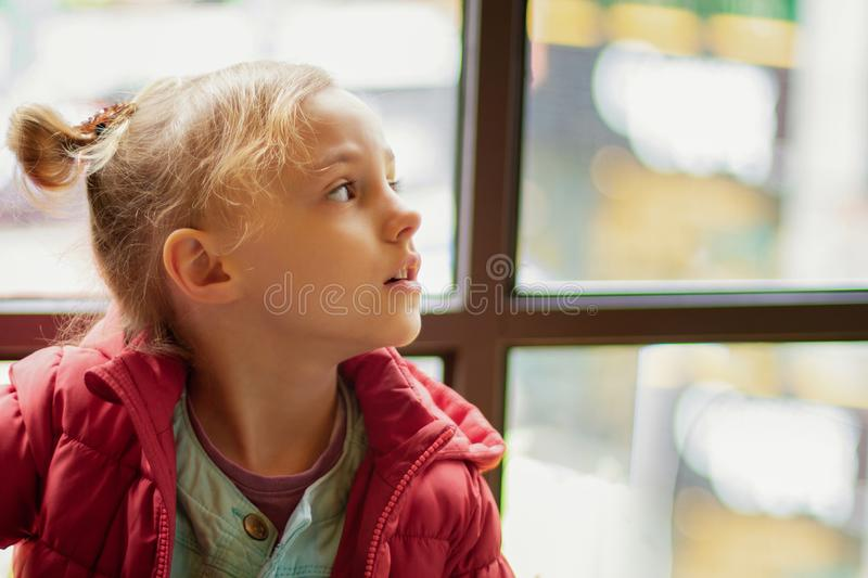 A little girl looks to the side by the window royalty free stock photos