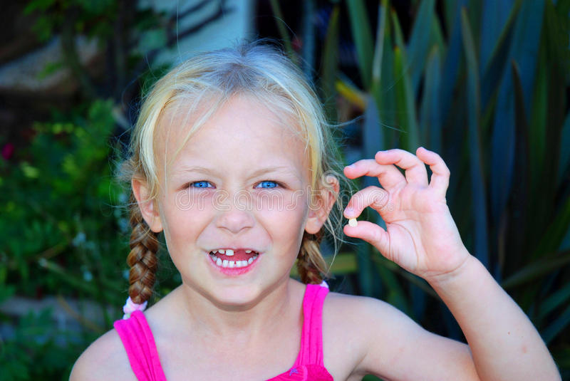 Little girl with lost baby tooth. A beautiful Caucasian little girl showing the exciting moment of her first lost baby tooth and the gap between her milk-teeth royalty free stock image