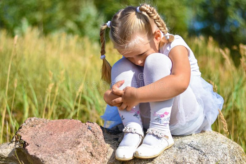 A little girl is lost in the street, sits on a rock and cries on a sunny day stock images