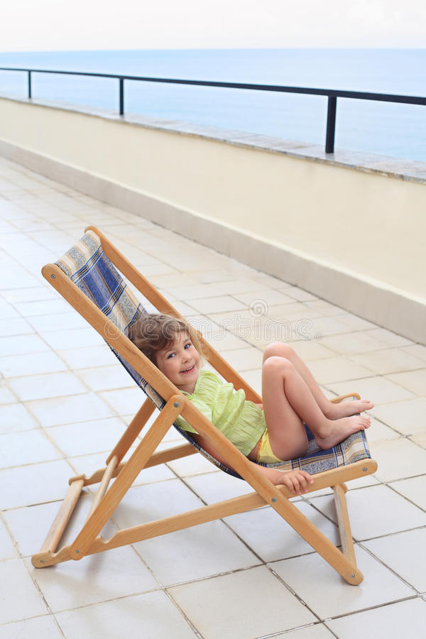 Little girl in lounge on veranda stock photography