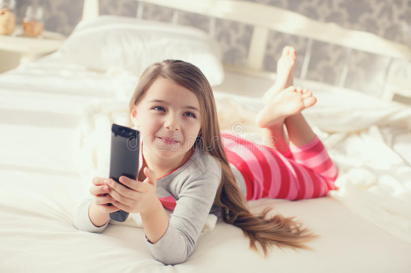 Little girl lying in bed with a remote control TV royalty free stock photo