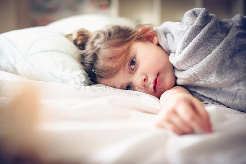 Morning in bed. Little girl lying in bed. Space for copy royalty free stock photo