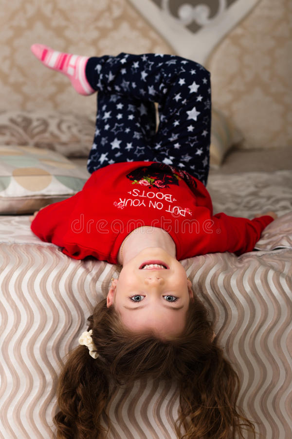 Download Little Girl Lying On The Bed Upside Down Stock Photo - Image: 83720674