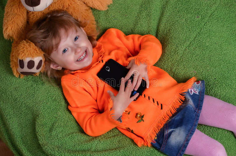 Little girl lying on a big green pillow stock image