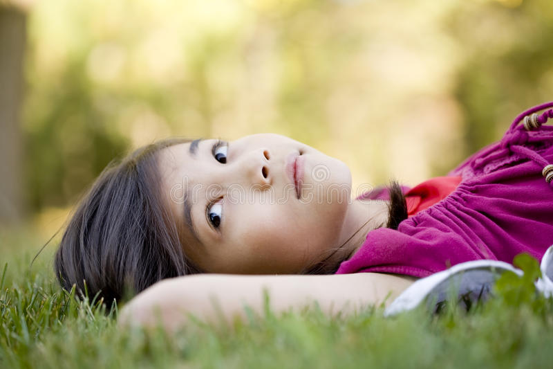 Little girl lying on grass stock photos