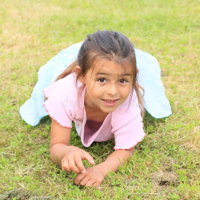 Little girl lying on grass royalty free stock image