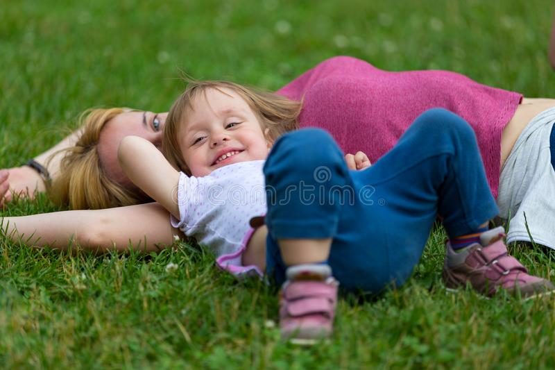 Little girl lying on the grass with her mother royalty free stock photo
