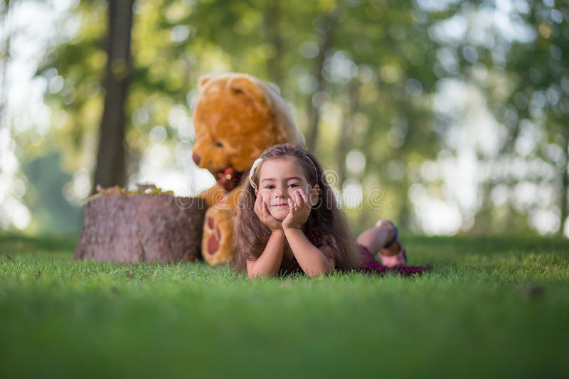 Little girl lying on the grass in the park royalty free stock photography