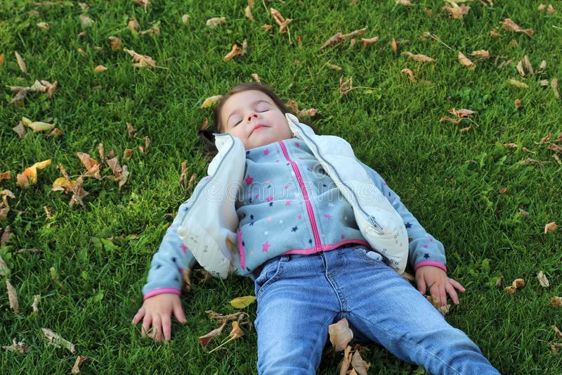 little girl lying on green grass and looking at the sky. Snow angel on the lawn with fallen leaves royalty free stock photos