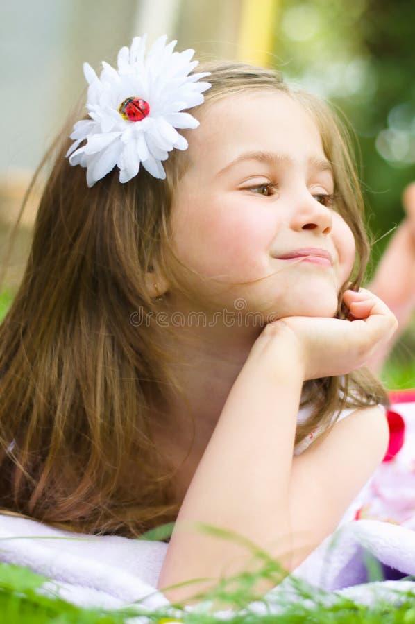 Little girl lying on green grass stock image