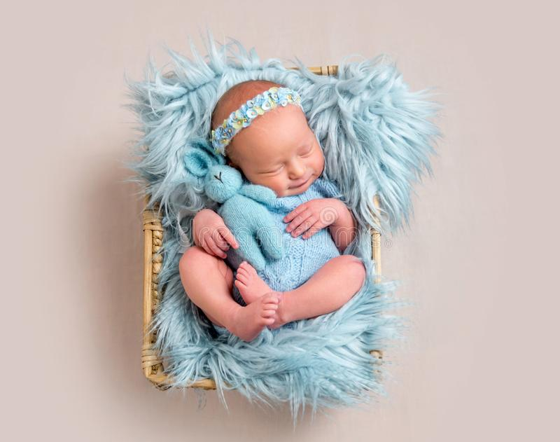 Little girl lying on her back and hug her toy, top view royalty free stock image
