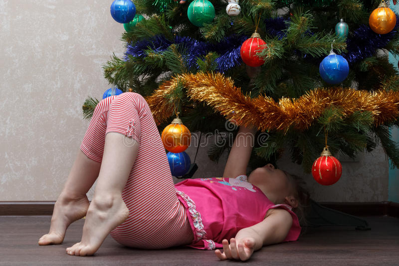 Little girl lying on her back under Christmas tree royalty free stock image