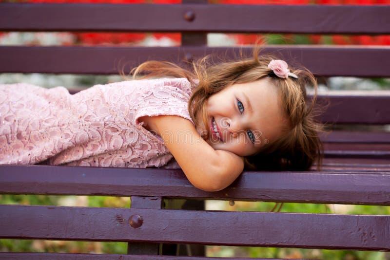 Little girl lying on park bench. royalty free stock photo