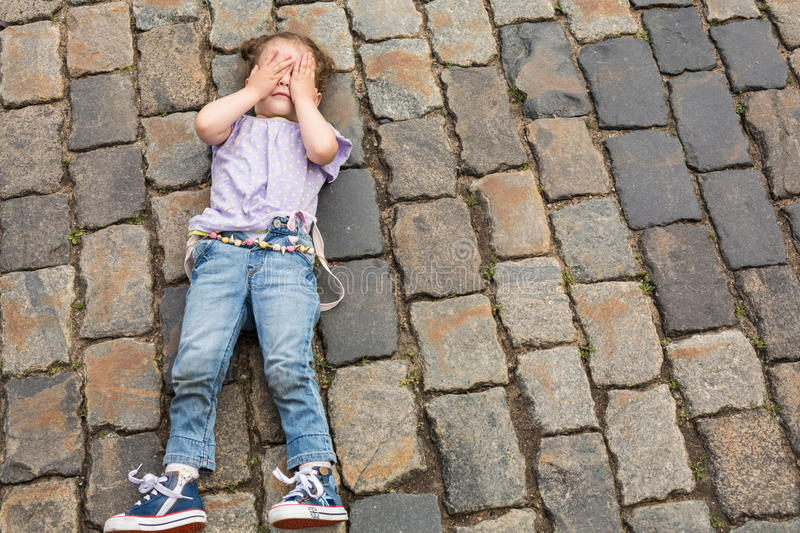 Little girl lying on the pavement stock images