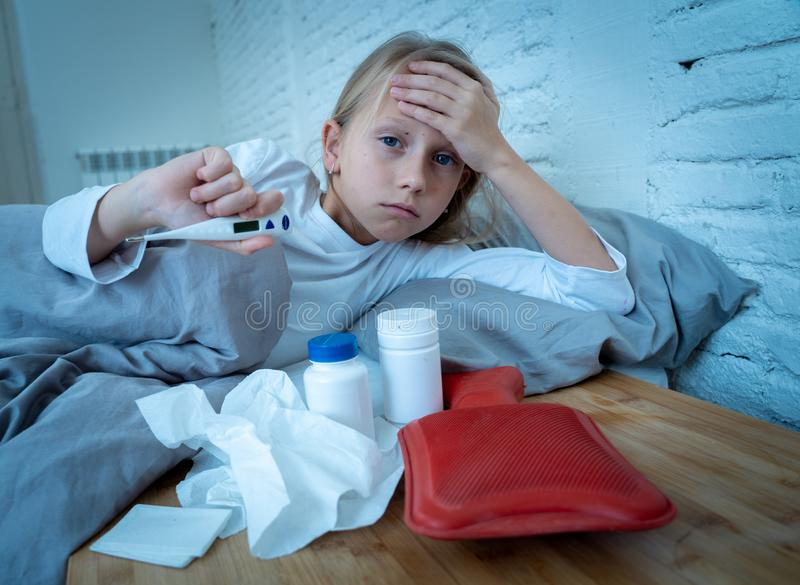 Little girl lying sick in bed feeling sick with high fever and headache having a cold flu royalty free stock photo