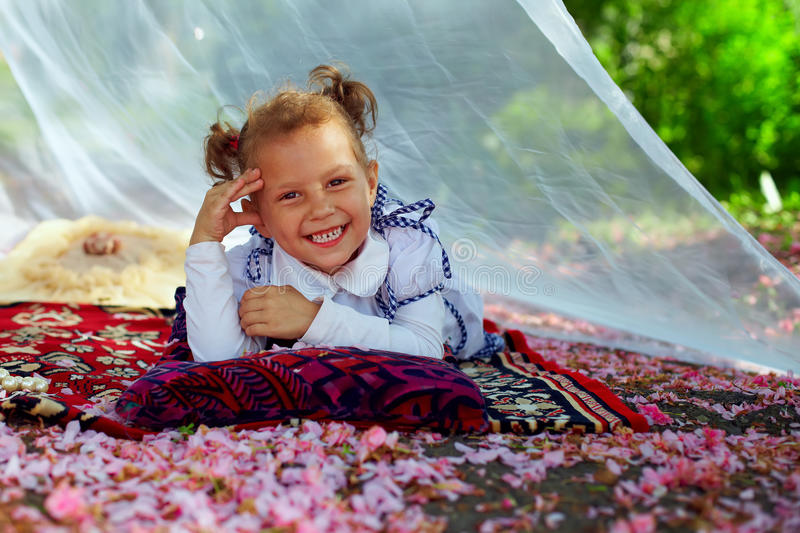 Little girl lying in summer arbor among petals royalty free stock photos