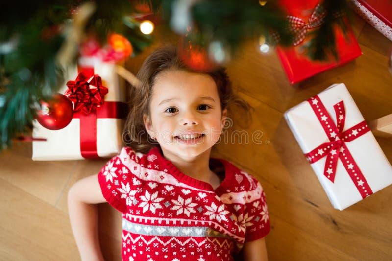 Little girl lying under Christmas tree among presents, royalty free stock photos