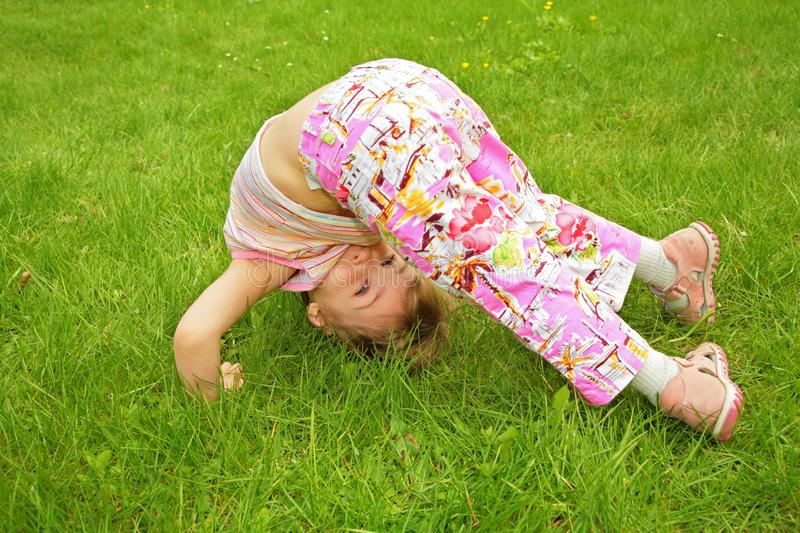 Little girl makes exercise on grass royalty free stock photography