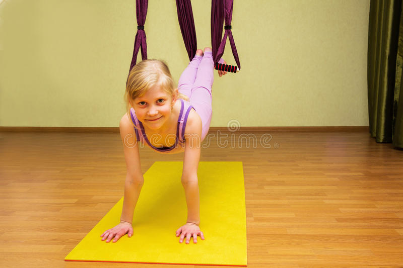 Little girl making aerial yoga exercises, indoor. Fly yoga royalty free stock photos