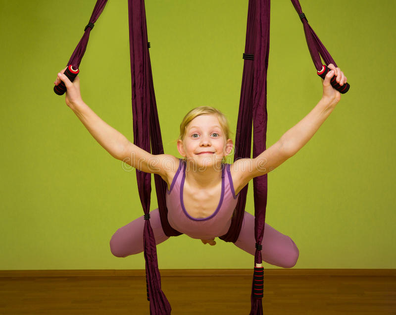 Little girl making aerial yoga exercises, indoor. Fly yoga royalty free stock photography