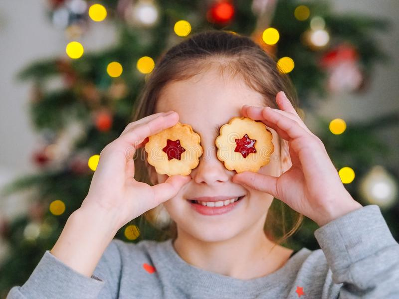 Little girl making cookies in room with Christmas lights stock images