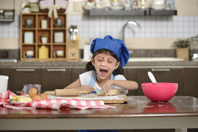 Little Girl Making Dough. Little asian girl making dough in the kitchen royalty free stock photography