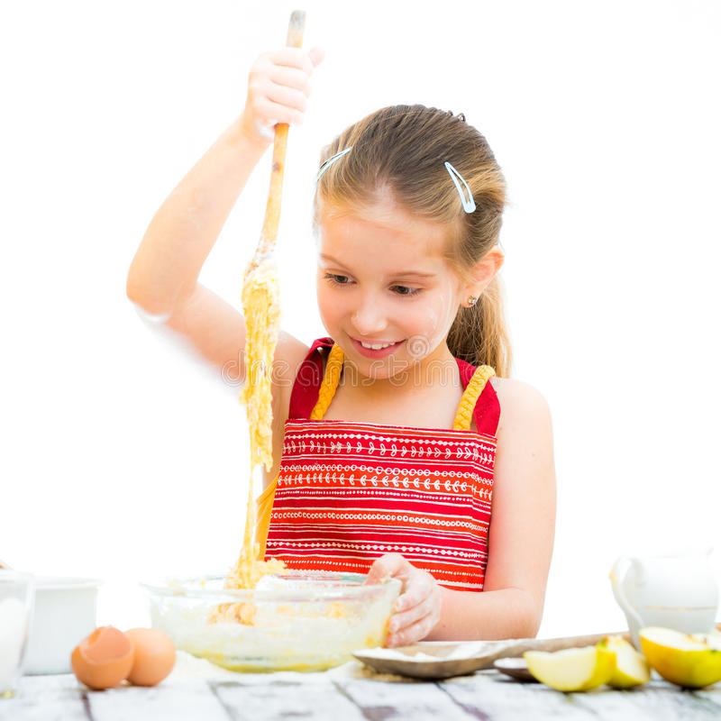 Little girl making dough. Cutre little girl making dough isolated on a white background royalty free stock photo