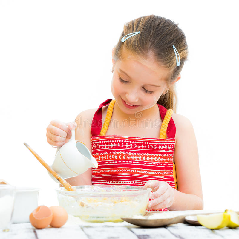 Little girl making dough. Cutre little girl making dough isolated on a white background royalty free stock images
