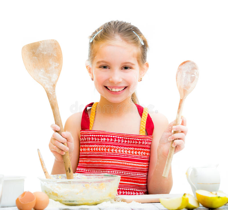 Little girl making dough. Cutre little girl making dough shows wooden spoons isolated on a white background stock photo