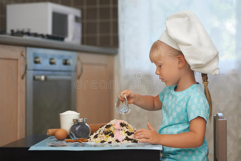 Little girl making dough in a shape of volcanoe.  royalty free stock photos
