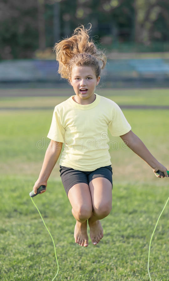 Little girl making exercising with skipping rope at stadium at summer day royalty free stock photo