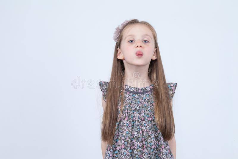Little girl is making faces. Funny expressions. Having fun. Preschooler in dress on white background. royalty free stock image