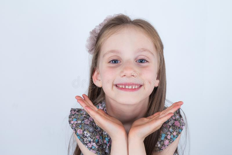 Little girl is making faces. Funny and happy expressions. Having fun. Preschooler in dress on white background. stock photography