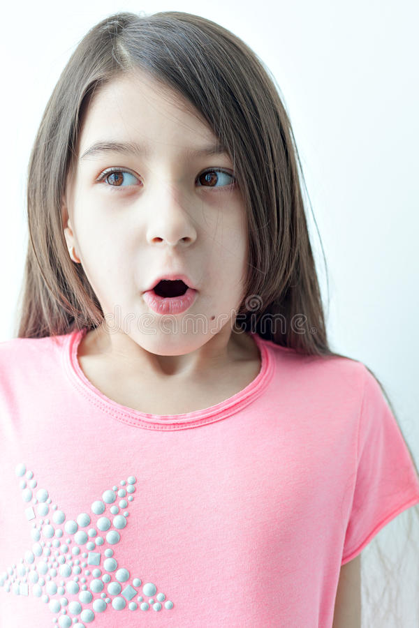 Little girl making a funny face. Emotions on the girl's face. The surprise and big eyes. White background royalty free stock image