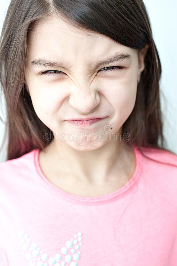 Little girl making a funny face. Emotions on the girl's face. wrinkle your nose. growl, and screwing up his eyes. White background stock photography
