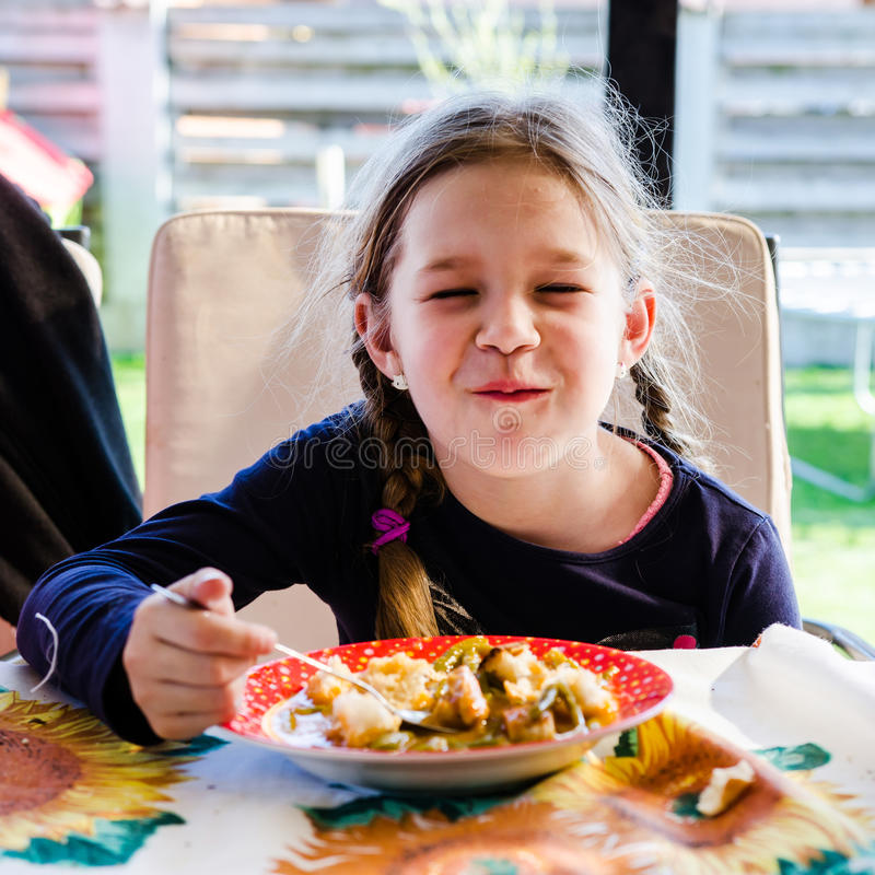 Little girl making funny faces while eating lunch. Little blonde girl making funny faces and eating lunch vegetarian lunch stock image