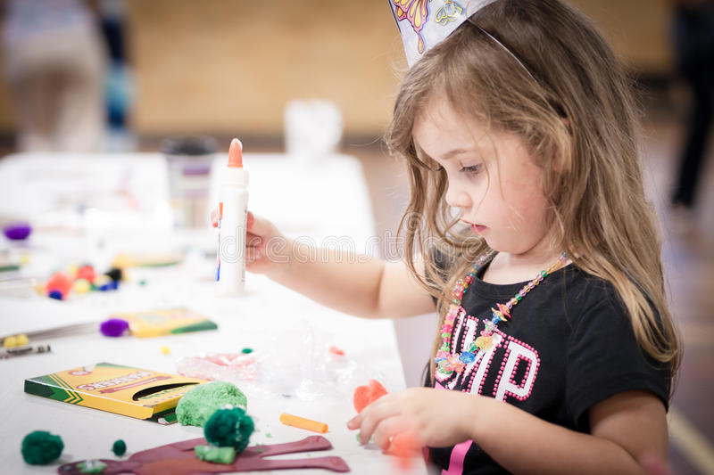 Little girl making handcraft at a table. At a kids party stock photos
