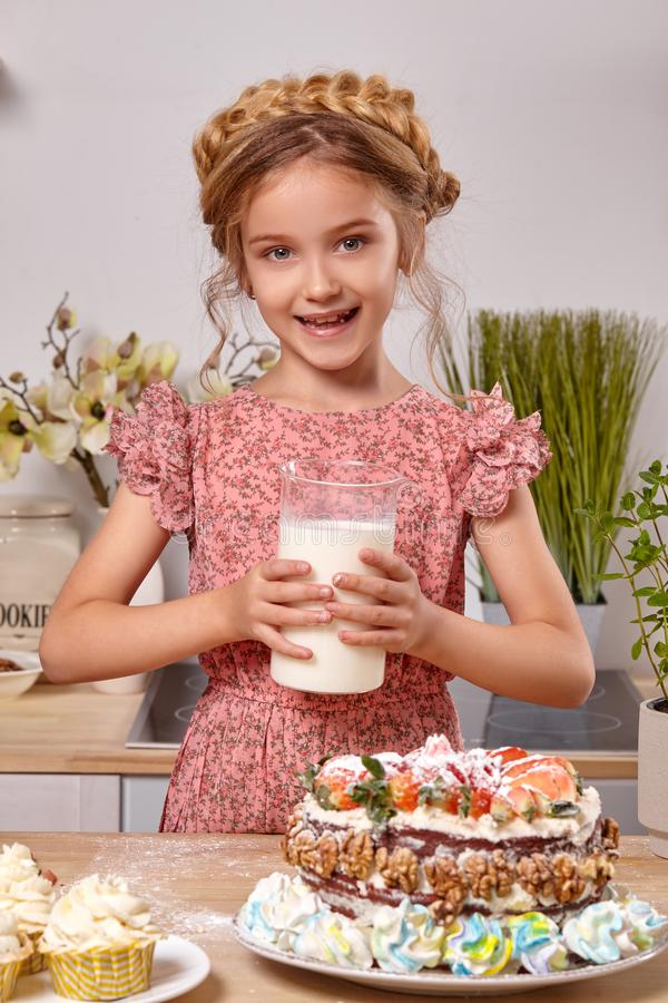 Little girl is making a homemade cake with an easy recipe at kitchen against a white wall with shelves on it. Amazing little girl wearing in a pink dress is stock photography