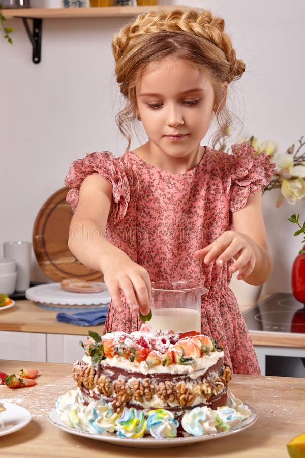 Little girl is making a homemade cake with an easy recipe at kitchen against a white wall with shelves on it. Little blond kid wearing in a pink dress is making royalty free stock photo