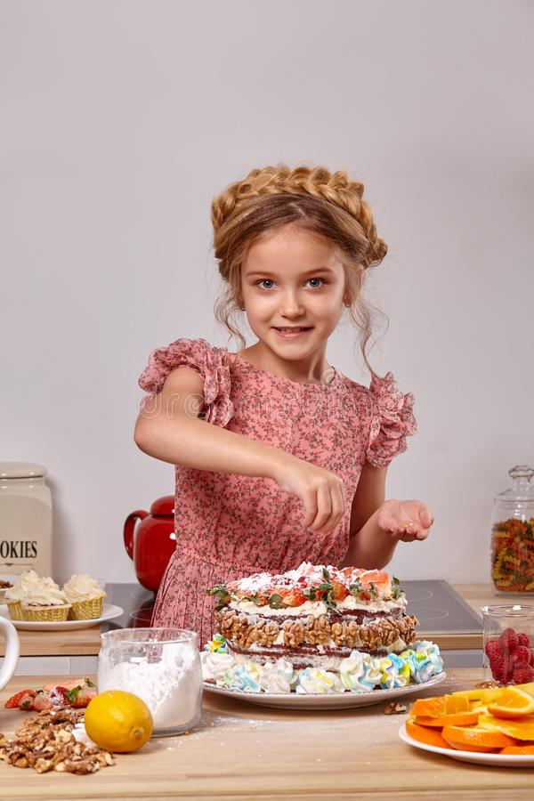 Little girl is making a homemade cake with an easy recipe at kitchen against a white wall with shelves on it. Cheerful child wearing in a pink dress is making a stock images