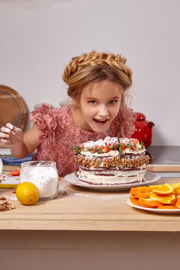 Little girl is making a homemade cake with an easy recipe at kitchen against a white wall with shelves on it. Little stylish girl with smeared in powdered sugar royalty free stock image