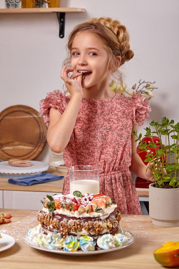 Little girl is making a homemade cake with an easy recipe at kitchen against a white wall with shelves on it. Little stylish girl wearing in a pink dress is stock photo