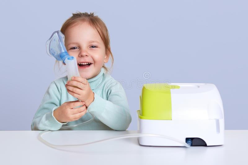 Little girl making inhalation with nebulizer at home, child suffers from asthma, uses inhaler, sits at white desktop, looks royalty free stock photo