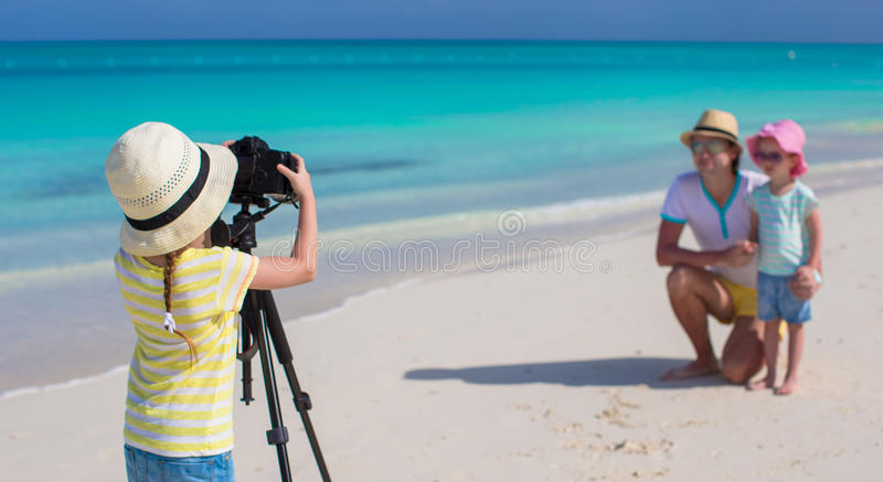 Little girl making photo of her dad and sister at royalty free stock image