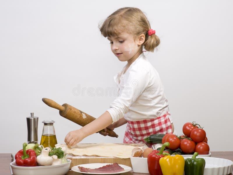 Little girl making pizza stock images
