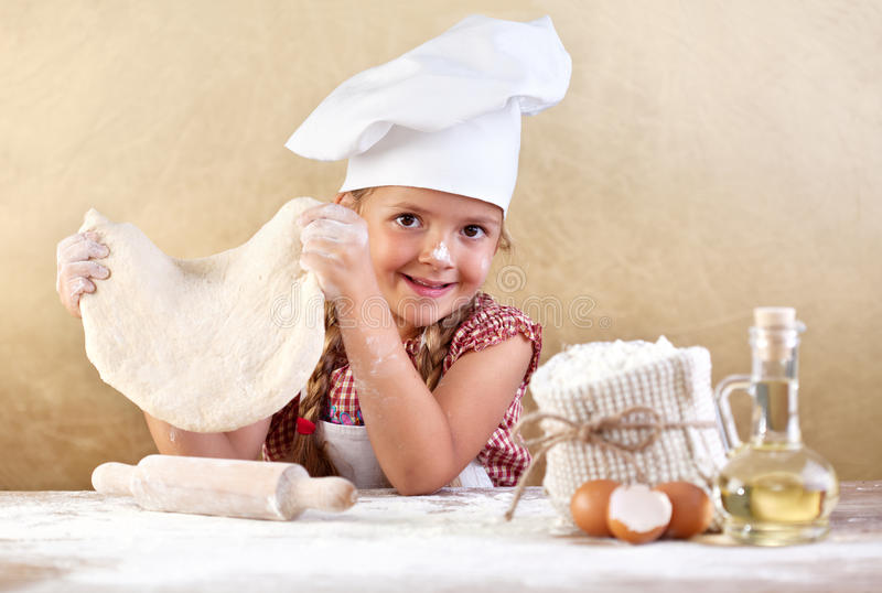 Little girl making pizza or pasta dough. Smeary with flour stock images